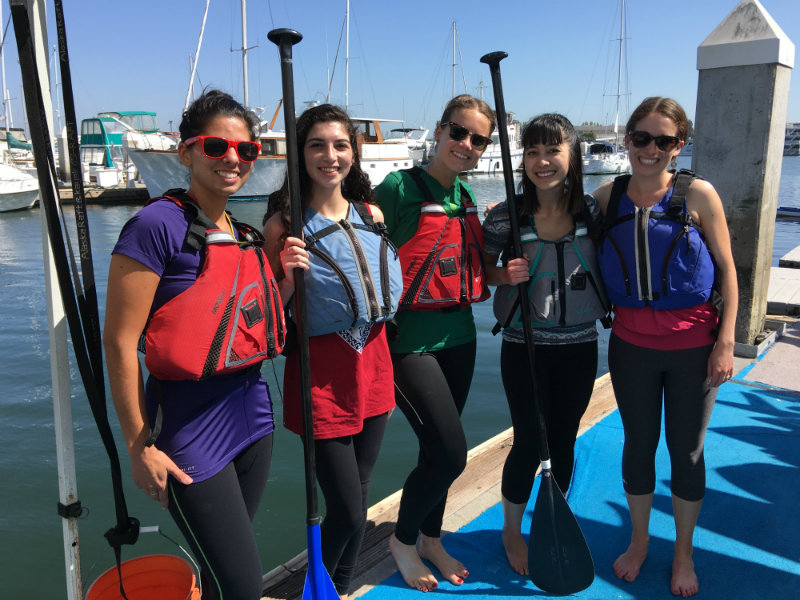 Team activity: paddle boarding. Lisa is wearing her cool Yogzi from Nova Yoga!
