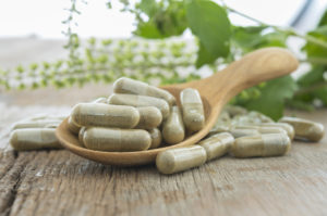 Moringa capsule in wooden spoon
