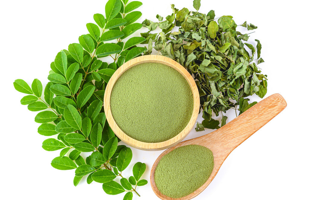 Moringa powder in wooden bowl with fresh Moringa and dried leaves on white background,Top view.