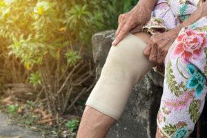 Woman adjusts knee brace on right leg