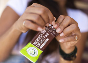 woman eating moringa bar