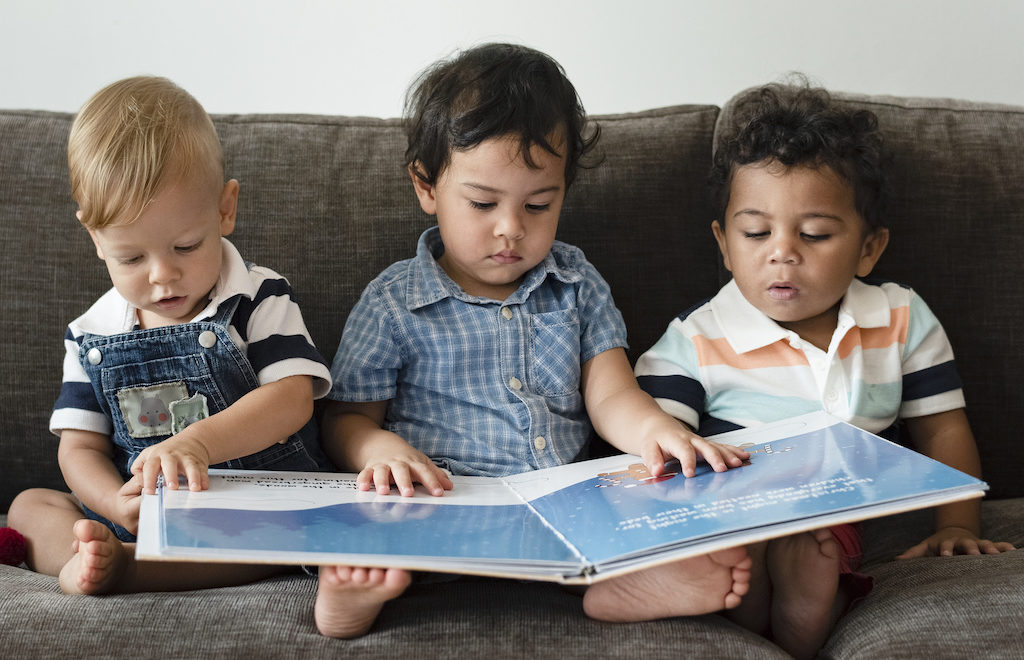 Three kids reading a book on the sofa