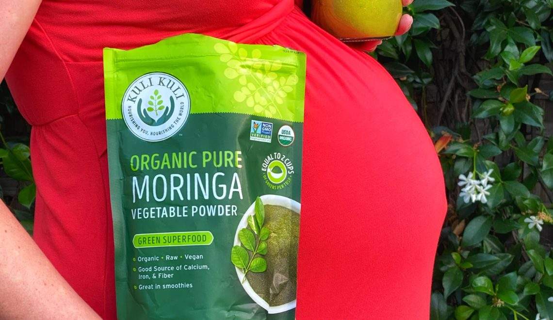 Pregnant woman in red dress with bag of moringa powder